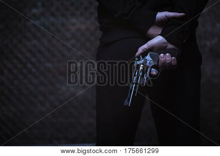 Preparing a robbery. Brutal wicked dark man covering a weapon behind his back while wearing all black clothes and waiting for someone