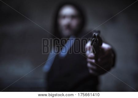 Give me money or die. Furious loaded savage man holding a weapon in his hand and pointing it at his victim while wearing black hoodie