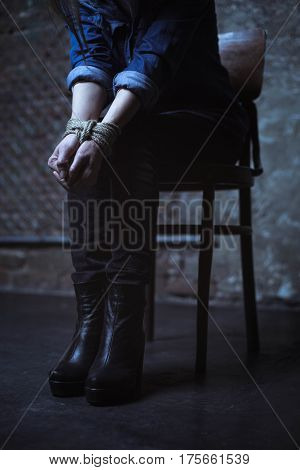 No way out. Weak protectless petite lady sitting in a dark room with her hands being tied up with a rope