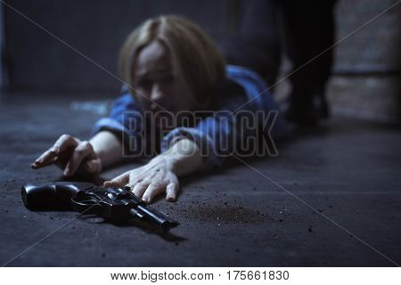 I can take it. Trapped powerless blonde woman trying reaching a gun for protecting herself while her captor dragging her pulling her away