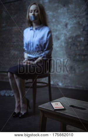 Maybe they are looking for me. Desperate weak abandoned girl trying taking a glimpse at who calling while being captivated in a dark room