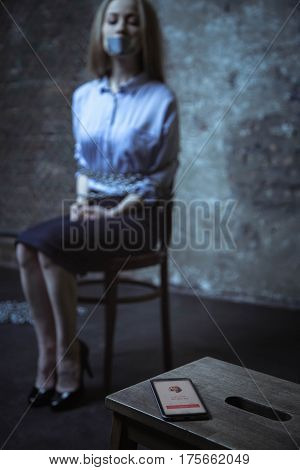 Important call. Trapped helpless miserable girl trying figuring out who calling while sitting in a dark room tied up to a chair