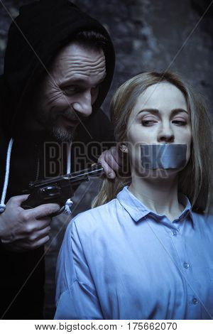 Be a good girl to survive. Irritated crooked wicked man telling his hostage complying while pointing a gun at her