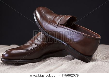 Footwear Concepts and Ideas. Pair of Brown Stylish Leather Penny Loafer Shoes Placed On Mesh Surface. Against Black Background. Horizontal Image