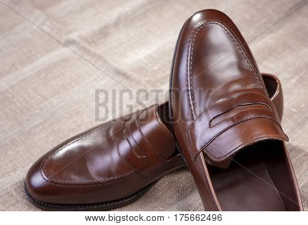 Footwear Concepts and Ideas. Pair of Brown Stylish Leather Penny Loafer Shoes Placed On Mesh Surface. Horizontal Image Orientation