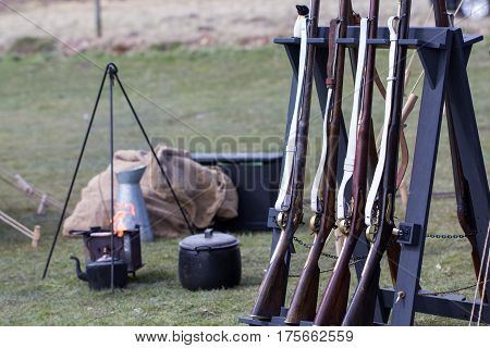 Reproduction vintage muskets at a military camp fire. Napoleonic war reenactment musket rifles. Selective focus on foreground.