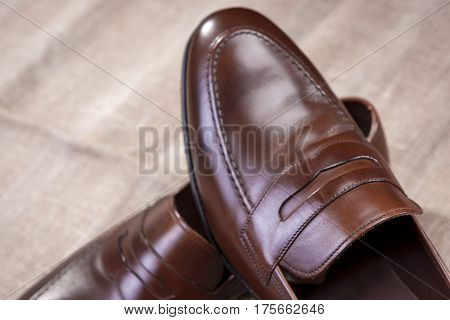 Footwear Concepts and Ideas. Closeup of Pair of Brown Stylish Leather Penny Loafer Shoes Placed On Mesh Surface.Horizontal Shot