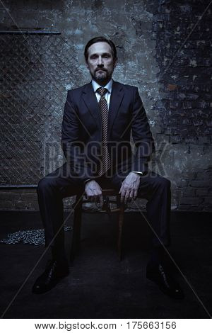 Super villain. Good looking brunette sharp gentleman wearing a classic suit and sitting on a chair in a dark room while holding a gun