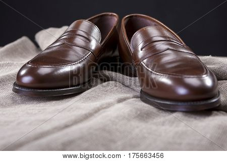 Shoes Concepts and Ideas. Closeup of Stylish Modern Brown Leather Penny Loafer Shoes Against Black Background. Horizontal Composition