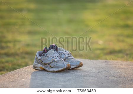 Old pair of grey sports shoes on cement floor in the park