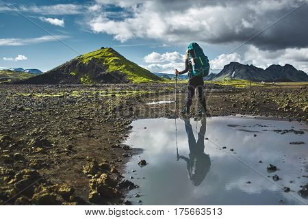 woman hiker on the trail in the Islandic mountains. Trek in National Park Landmannalaugar, Iceland. valley is covered with volcano asher