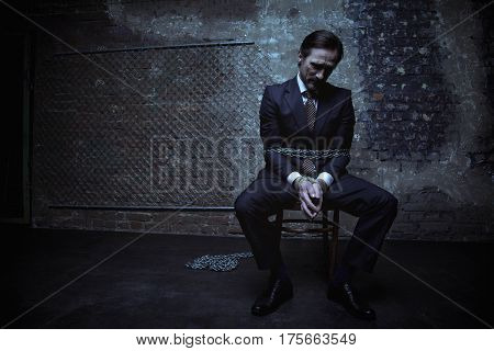 Sorrow found me. Elegant rich scared man looking hopeless while being captured in a dark placed and loaded with chains
