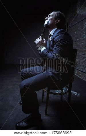 I have a chance now. Scared desperate captured gentleman sitting in a dark room while being tied up to a chair with chains and holding a gun in his hands