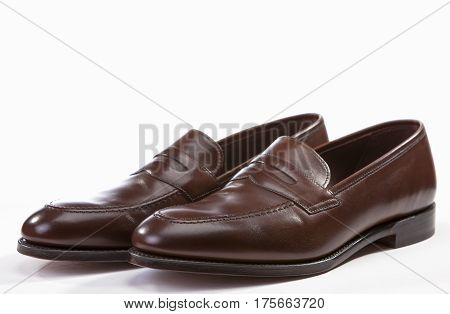 Footwear Concepts. Closeup of Leather Stylish Brown Penny Loafer Shoes Together Against White Background. Horizontal Image Orientation