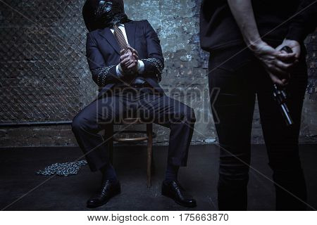 Please, let me live. Terrified well dressed rich gentleman being captured in a dark room, tied up and defenseless while his abductor staying in front of him