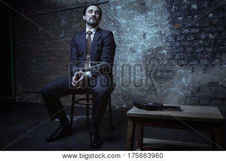 Planning my own saving. Smart interested well dressed man looking at the weapon lying on the table nearby while being kept hostage in a dark room