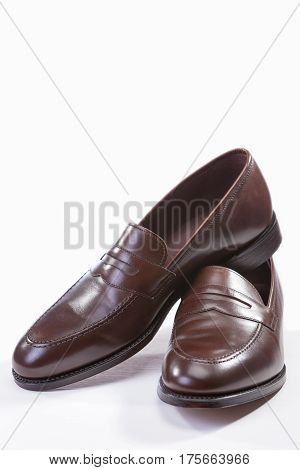 Footwear Concepts. Leather Stylish Brown Penny Loafer Shoes Together Against White Background. Vertical Image Orientation