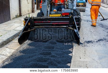 light truck laying fresh bitumen and asphalt at road construction site