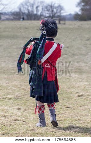 Scots guard piper from a war reenactment group on the battlefield with bagpipes. In reproduction traditional uniform.