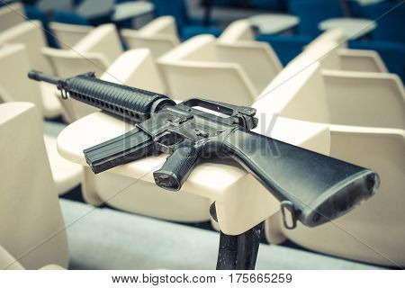 A rifle in a lecture room / Armed campus concept