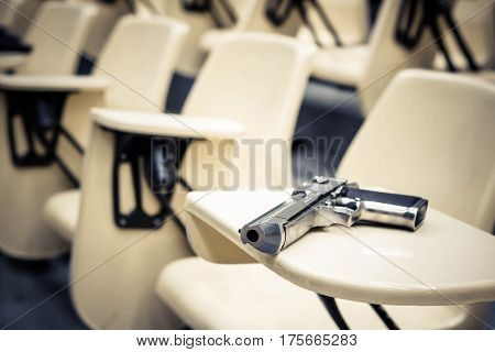 A gun in a lecture room / Armed campus concept