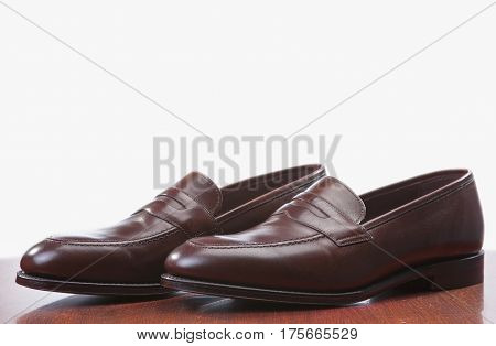 Footwear Concepts. Closeup of Pair of Stylish Brown Penny Loafer Shoes Against White. Placed on Wooden Reflecting Surface. Horizontal Image