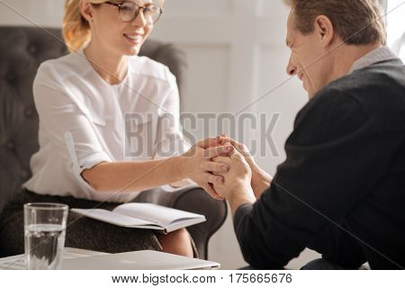 Kinesthetic communication. Cheerful positive professional therapist smiling and holding hands of her patient while gaining his thrust