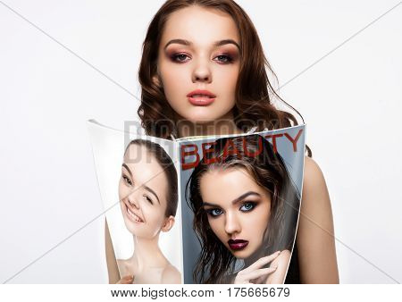 Beautiful girl holding fashion beauty magazine with her portrait on magazines cover on white background