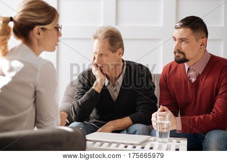 Problems in relationships. Serious nice thoughtful man sitting with his boyfriend on the sofa and listening to the therapist while trying to cope with problems
