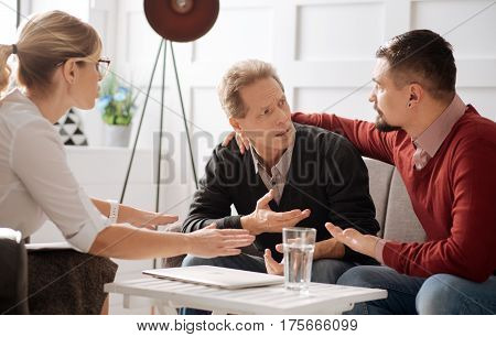 Gay couple. Cheerless moody bearded man sitting near his boyfriend and hugging him while visiting together a psychologist