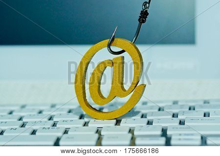 Email sign with a fish hook on computer keyboard. Email security and countermeasure concept