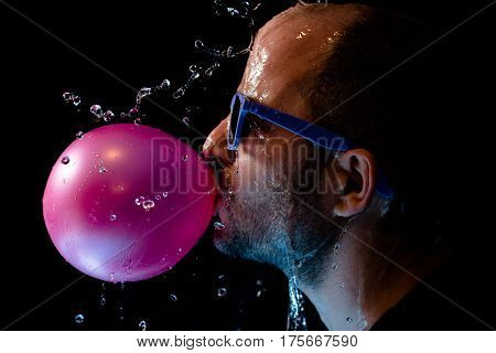 Portrait of a man with sun glasses chewing gum and being thrown water in the face against a black background