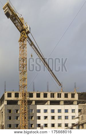 Building and Construction Concepts. Construction Building Site With Industrial Mid-Size Crane.Vertical Image