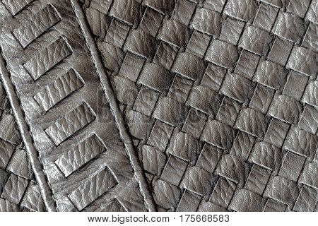 Texture of genuine dark wicker leather close-up and details with stitches of male handbag. For background, backdrop, substrate, use of composition. Concept of shopping, manufacturing, lifestyle,