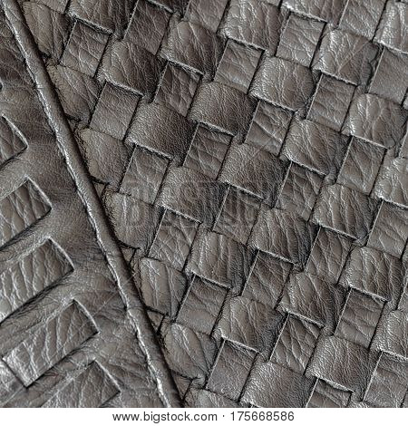 Texture of genuine dark wicker leather close-up and details with stitches of male handbag.