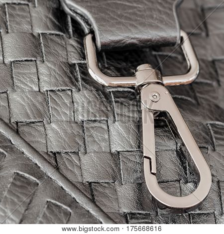 Texture of genuine dark wicker leather close-up and clasp, buckle of male handbag.