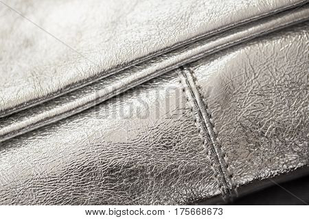 Close-up texture of evening silver handbag, clutch from genuine leather. For background, backdrop, substrate, use of composition. Concept of shopping, manufacturing, lifestyle, holiday, weekend