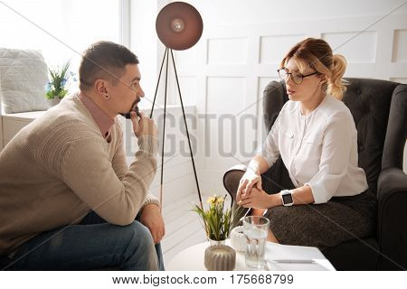 Psychological advice. Thoughtful handsome brunette man holding his chin and listening to a psychologist while looking for advice