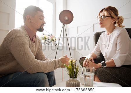 Looking for a solution. Cheerless moody bearded man sitting in the armchair and sharing his concerns with a psychologist while trying to cope with his problems