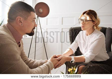 Feel my support. Attractive sympathetic female psychologist looking at her patient and holding his hands while supporting him