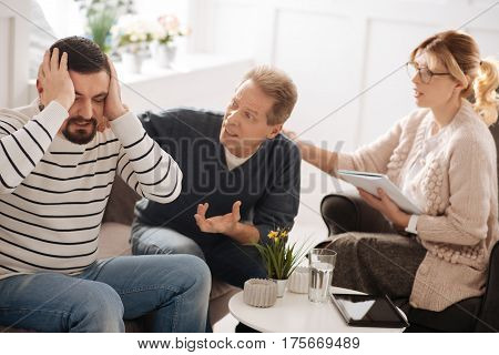 It is enough for me. Unhappy emotional bearded man sitting on the sofa and holding his head while having a quarrel with his boyfriend
