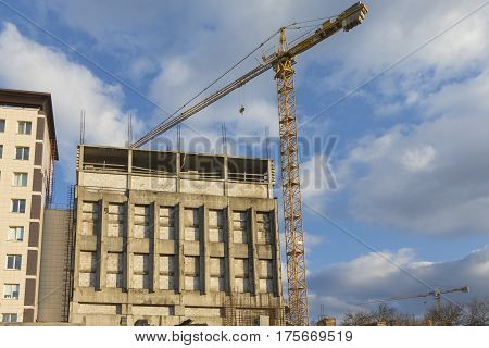 Architecture and Construction Concepts and Ideas. Industrial Construction Site With Mid-Size Crane In Process.Horizontal Image Composition