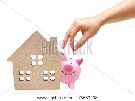 Hand putting a golden coin to a pink piggy bank with a wooden house / Saving money for buying a house concept