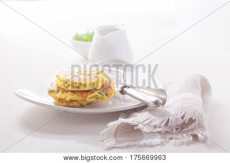 Healthy vegetarian zucchini fritters served on a table