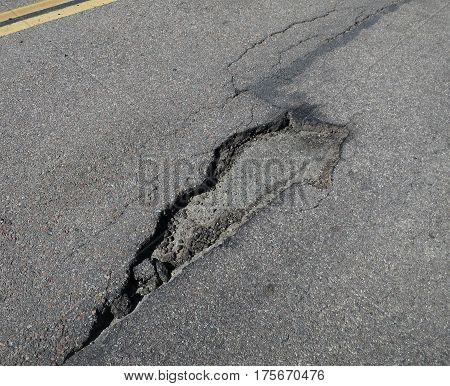 Large pothole in asphalt street in need of repair.