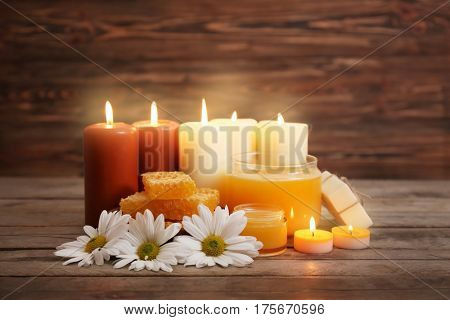 Beautiful composition of alight candles and honey treatments on wooden table