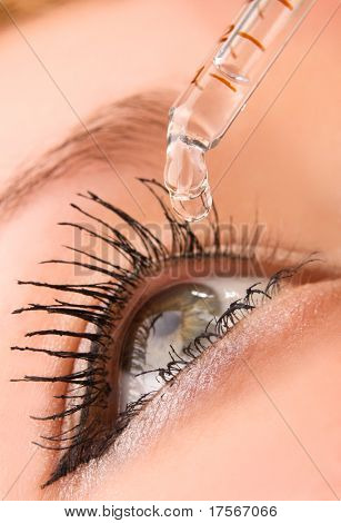 Closeup of eyedropper putting liquid into open eye poster