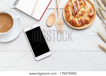 Top View Danish Pastries, Coffee, Note Book And Smartphone On White Wooden Table