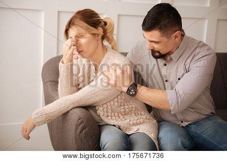 Feeling of depression. Unhappy depressed sad woman sitting with her husband and holding her forehead while thinking about her problems