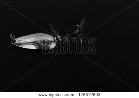 An exhibition of pirated copies of fishing metal spoon baits. Bait for fishing in the shape of a spoon with a hook on a black background.